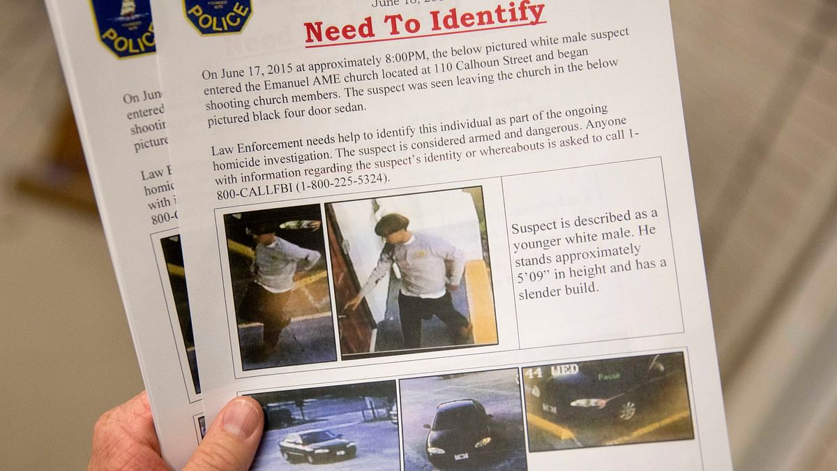 An officer holds a flier distributed to media, on Thursday, with surveillance footage of a suspect wanted in the shooting. (Photo: AP)