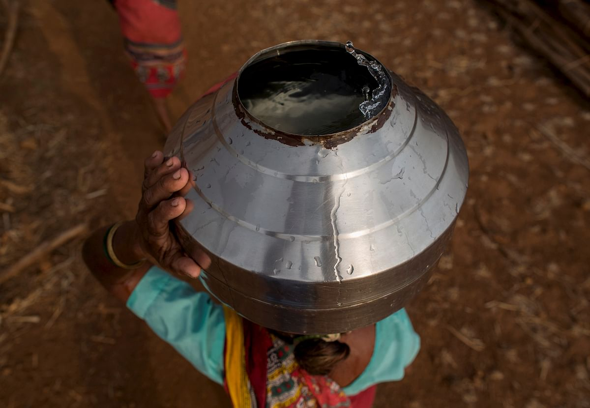 Bhaagi, third wife of Sakharam Bhagat, carries a metal pitcher filled with water from a well outside Denganmal village, Maharashtra, India, April 20, 2015. (Photo: Reuters)