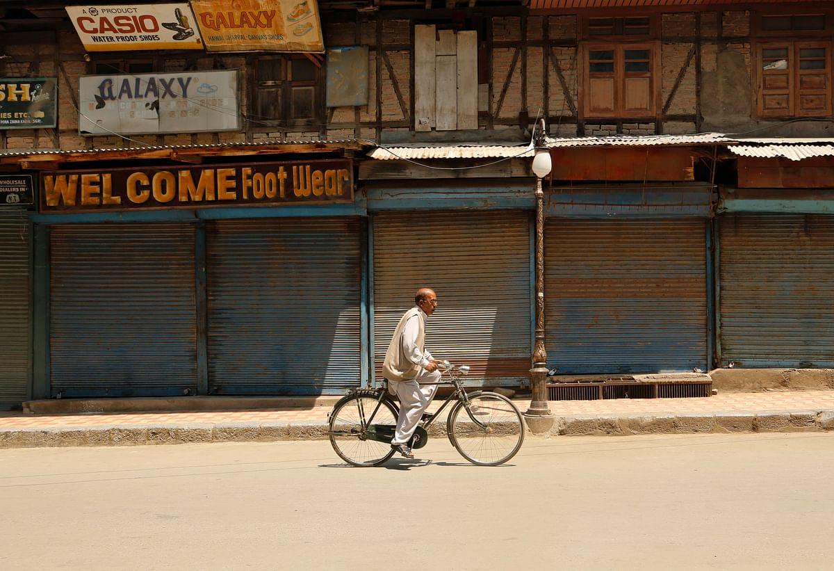 A civilian rides on his bicycle through a closed market during a strike in Srinagar. (Photo: AP)