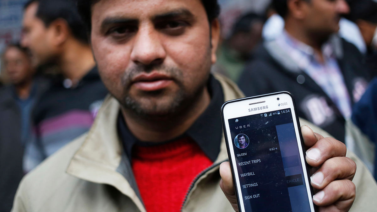 An Uber taxi driver shows the application software on his mobile phone.