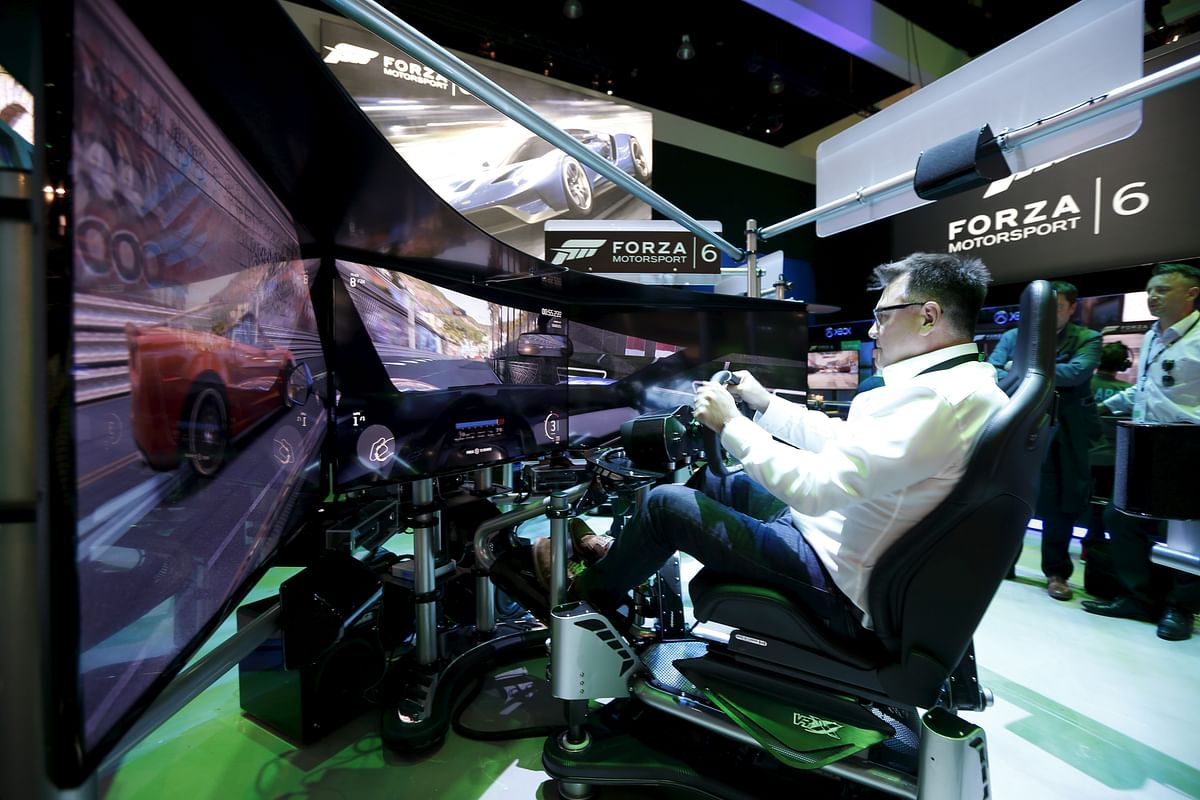 """A man plays the """"Forza Motorsport 6"""" video game simulator at the Microsoft Xbox booth. The game competes with PlayStation's GT 6. (Photo: Reuters)"""