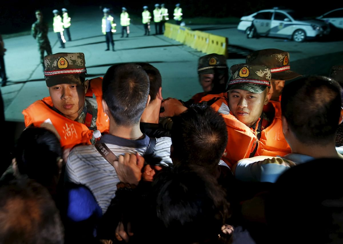Family members of passengers of the Eastern Star push a cordon of paramilitary police as they march as they marched towards the site of the sunken cruise ship in the Yangtze River to demand news of missing relatives  in the Jianli section of the Hubei province, China. (Photo: Reuters)