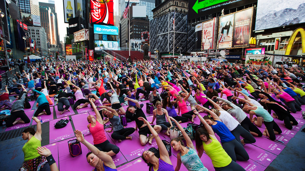 People take part in a group yoga practice on the morning of the summer solstice in New York's Times Square, June 21, 2013. (Photo: Reuters)