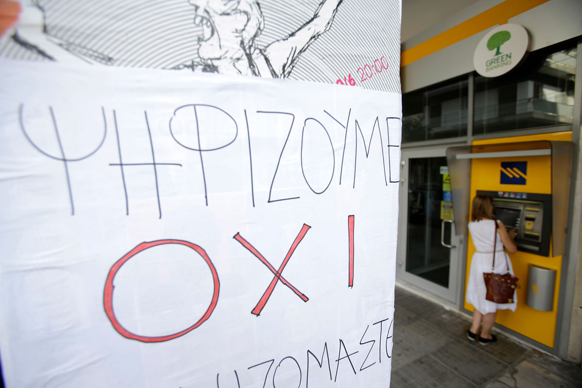 A woman uses an ATM of a closed bank as a sign that reads: ''We vote NO'' referring to the upcoming referendum, in Athens. (Photo: AP)