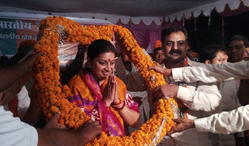 """Union HRD Minister Smriti Irani, who's in charge of education, being garlanded by party workers. (Courtesy:<a href=""""https://www.facebook.com/Smriti.Irani.Official?_rdr"""">Facebook.com/Smriti.Irani.Official</a>)"""