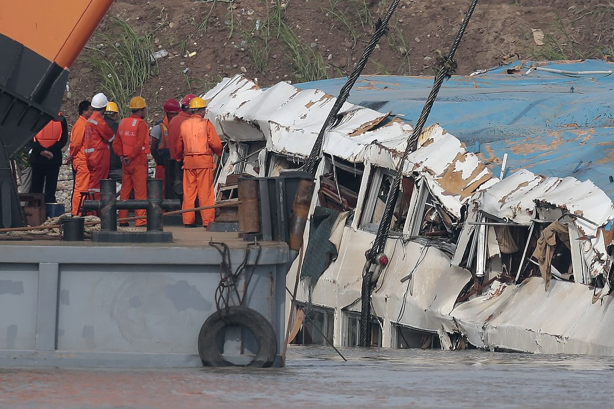 Rescue workers look on as a crane pulls the Eastern Star out of the Yangtze River in China. (Photo: Reuters)