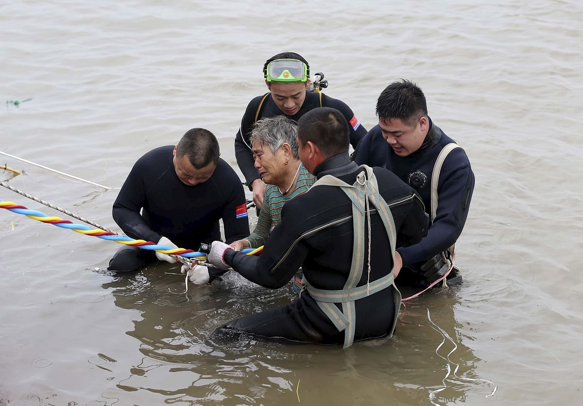 Rescue divers pull one of the 14 survivors out of the water, as 339 people reportedlyremain missing. (Photo: Reuters)