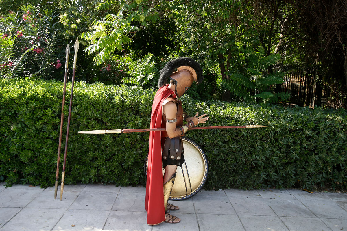 Ioakim Mylonopoulos an unemployed store owner, dressed as an ancient Spartan warrior who poses for photographs with tourists, fixes his costume, in Athens. (Photo: AP)