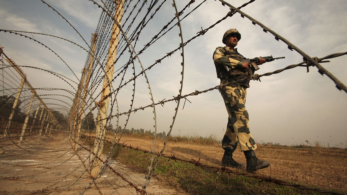 An Indian Border Security Force soldier patrols the fenced border with Pakistan. (Photo: Reuters)