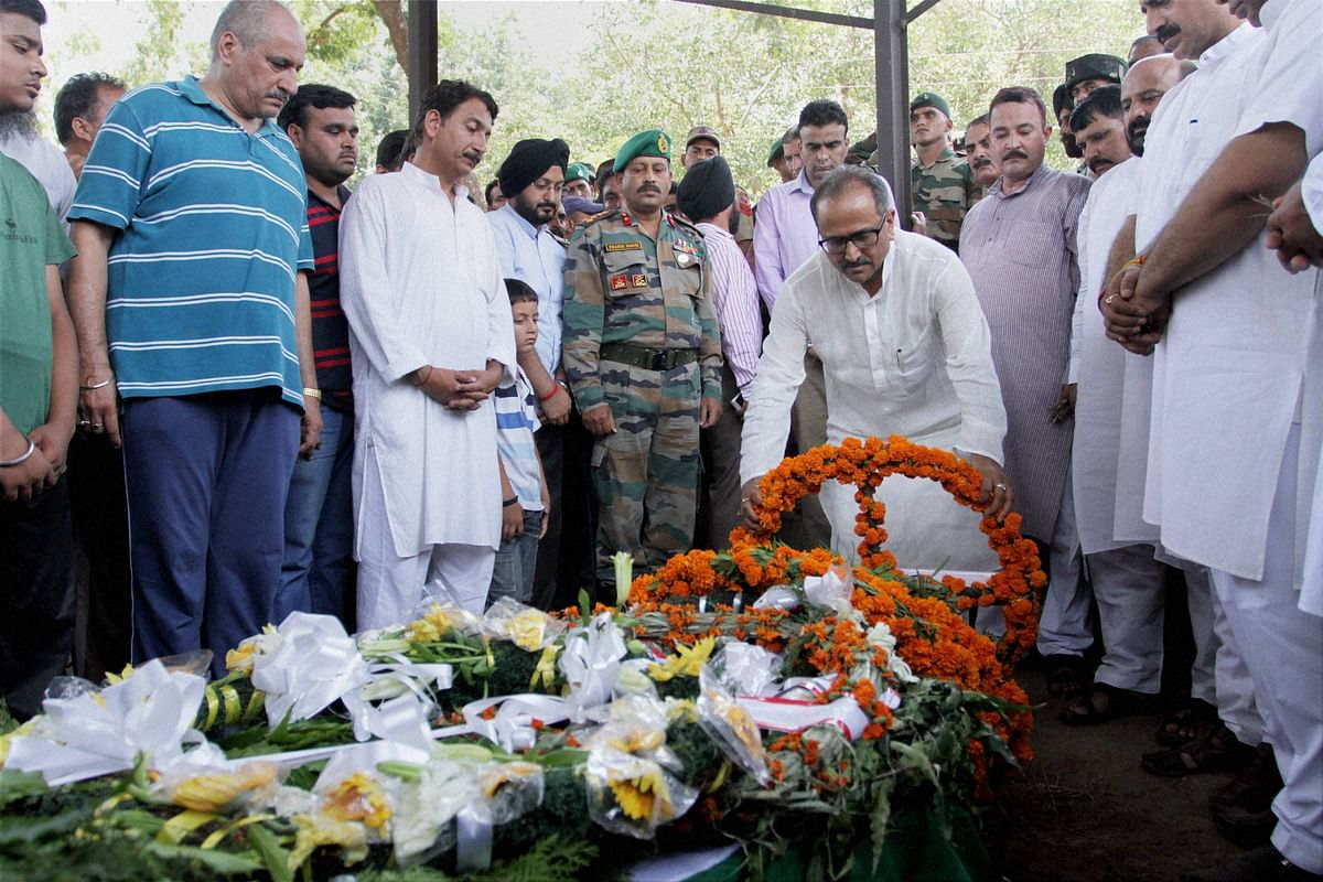 J & K Dy Chief Minister Nirmal Singh paying tribute, in Jammu on Sunday, to the soldier Sat Pal Bhasin, who was killed in an ambush in Manipur (Photo: PTI)