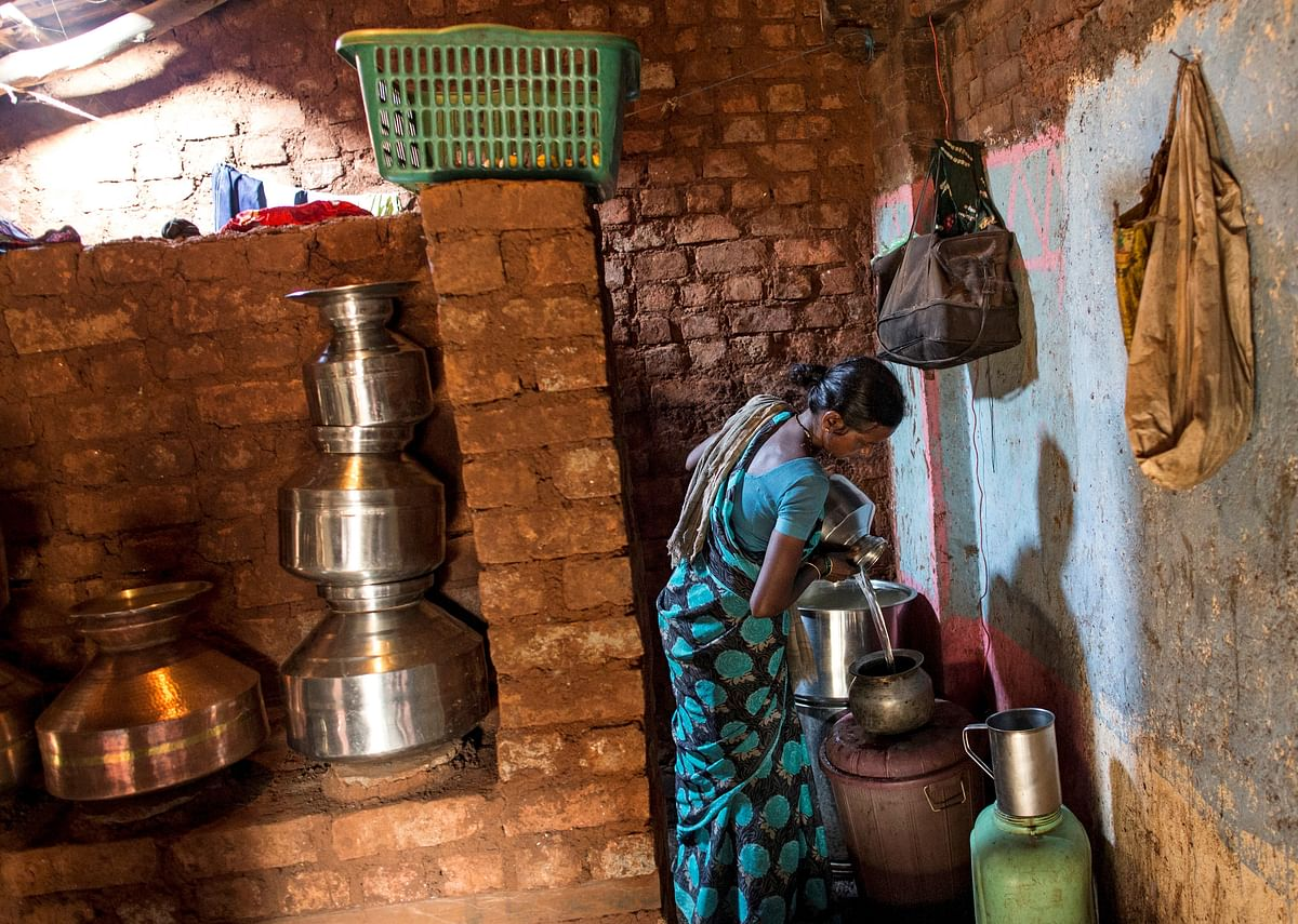 Shivarti, second wife of Namdeo, empties a water pitcher as she gets ready to fill water from a well outside Denganmal village, Maharashtra, India, April 21, 2015. (Photo: Reuters)