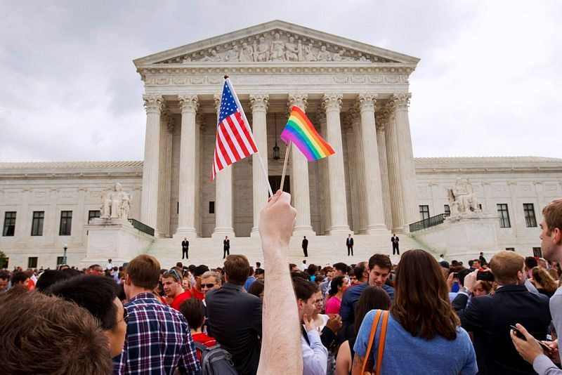 A man holds a U.S. and a rainbow flag outside the Supreme Court in Washington after the court legalised gay marriage nationwide in USA.  (Photo: AP)
