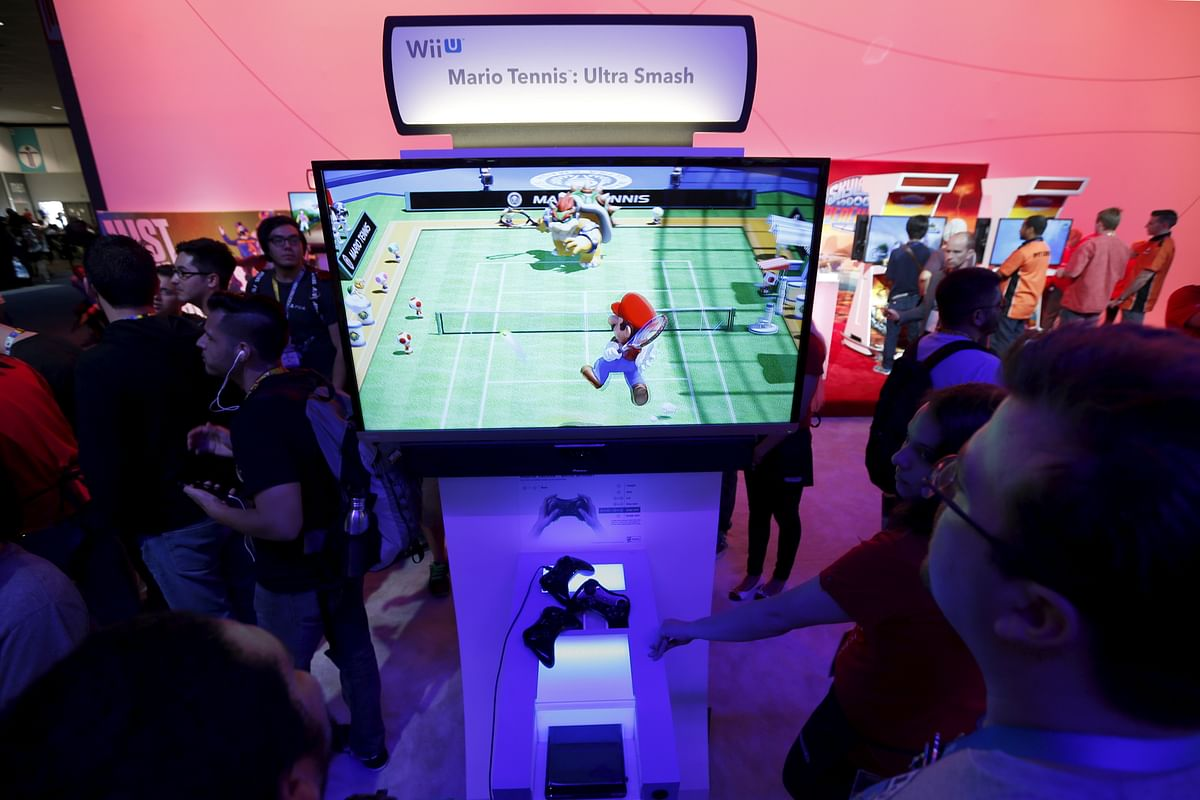 """People play """"Mario Tennis: Ultra Smash"""" Wii video game at the Nintendo booth. (Photo: Reuters)"""