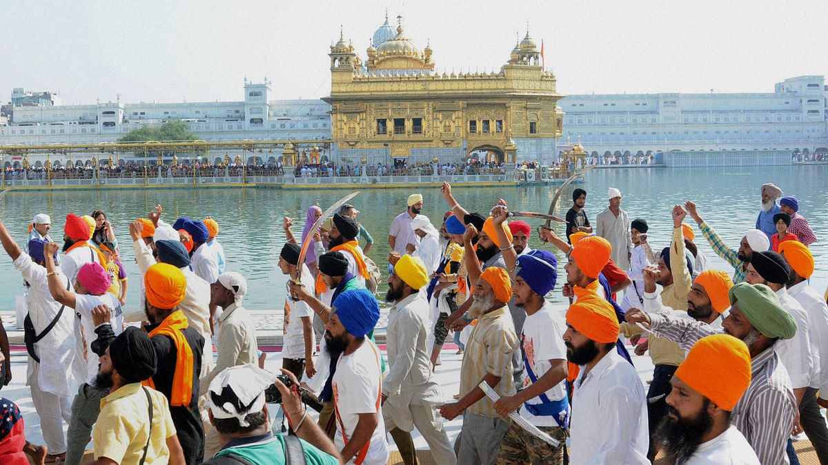 Sikh youth brandishing swords at the Golden temple. (Photo: PTI)