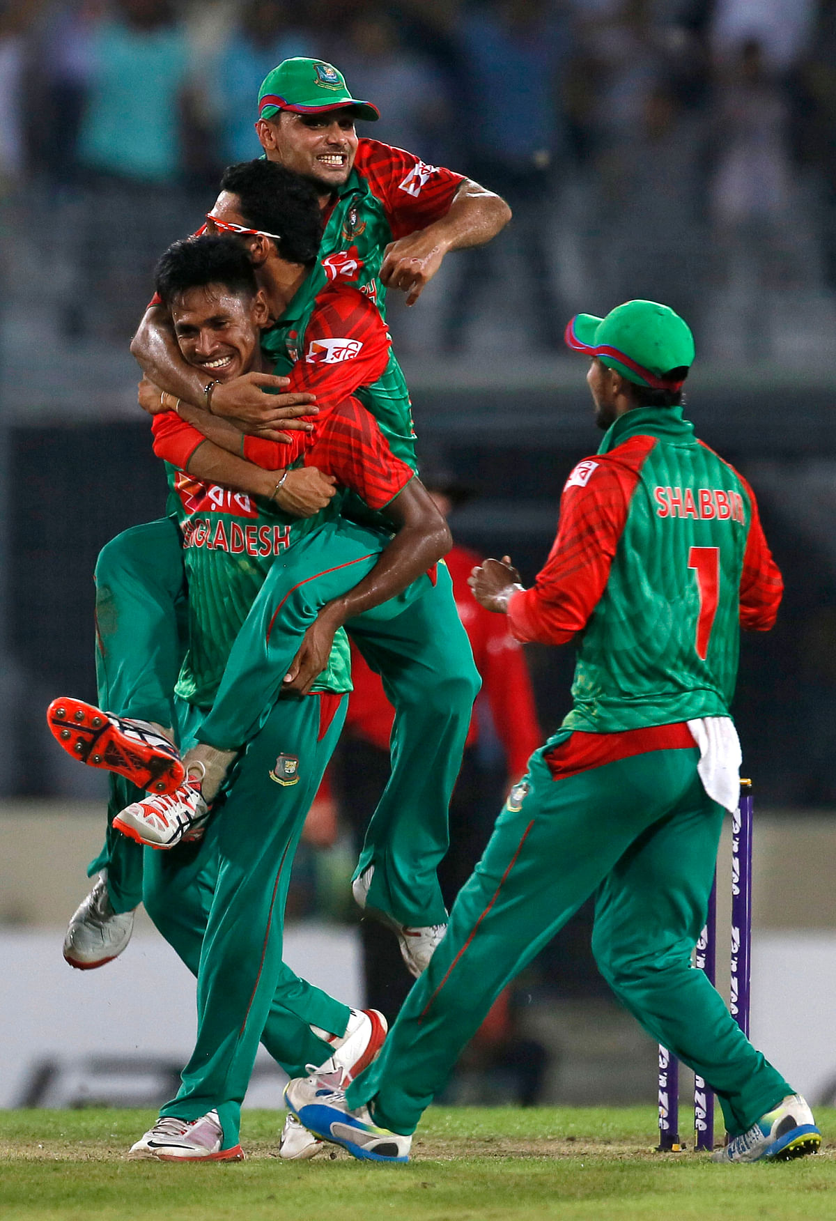 Bangladesh's Nasir Hossain, top, and captain Mashrafe Mortaza, center, jumps on Mustafizur Rahman as they celebrate the dismissal of Ravindra Jadeja. (Photo: AP)