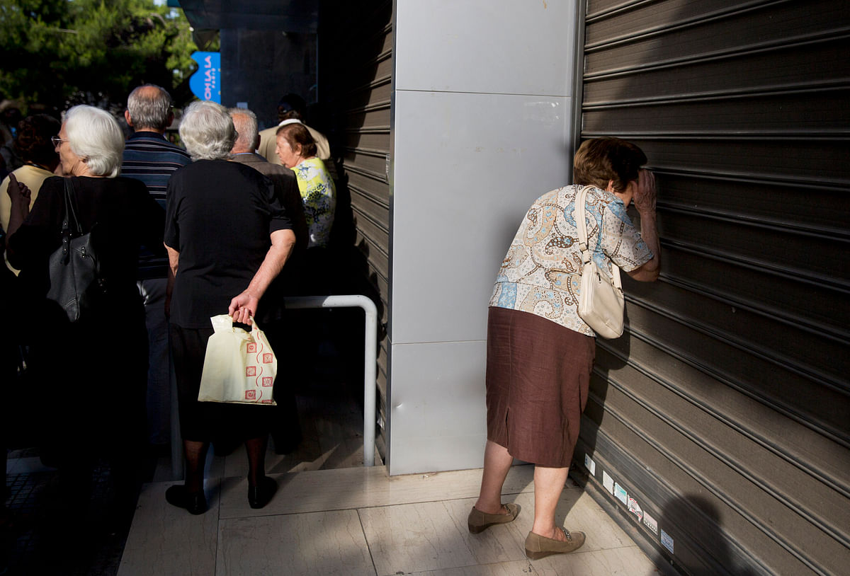 An elderly woman looks through the closed shutters of a bank as others, who usually get their pensions at the end of the month, wait outside a closed bank in Athens, Monday, June 29, 2015. (Photo: AP)