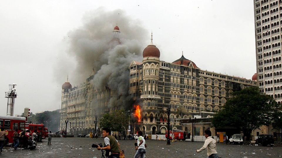 People run past burning Taj Mahal Hotel in Mumbai during the 26/11 terror attacks. (Photo: Reuters)