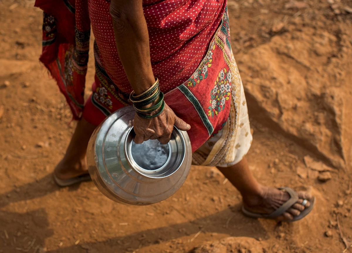 Sakhri, second wife of Sakharam Bhagat, carries an empty metal pitcher as she walks to fetch water from a well outside her village in Denganmal, Maharashtra, India, April 20, 2015. (Photo: Reuters)