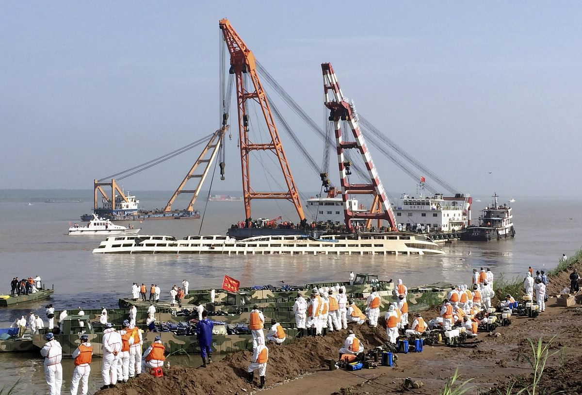 Cranes lift the Eastern Star out of the Yangtze river in China as rescue workers look on. (Photo: Reuters)