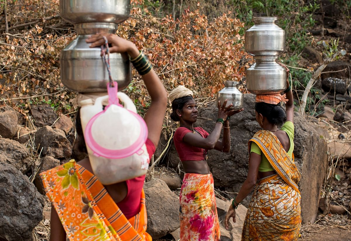 A woman helps another in carrying metal pitchers filled with water from a well outside Denganmal village, Maharashtra, India, April 20, 2015. (Photo: Reuters)