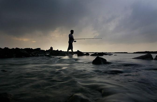 A fisher man catching fish in the Arabian Sea, Mumbai.