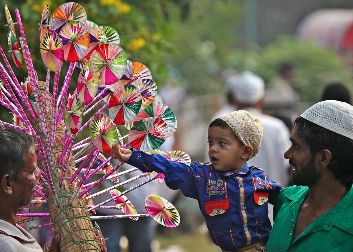 A Muslim boy buys a paper fly-wheel during the celebrations to mark Eid al-Adha in the northern Indian city of Chandigarh October 6, 2014. Muslims around the world celebrate Eid al-Adha by the sacrificial killing of sheep, goats, cows and camels to commemorate Prophet Abraham's willingness to sacrifice his son Ismail on God's command. (Photo: Reuters)