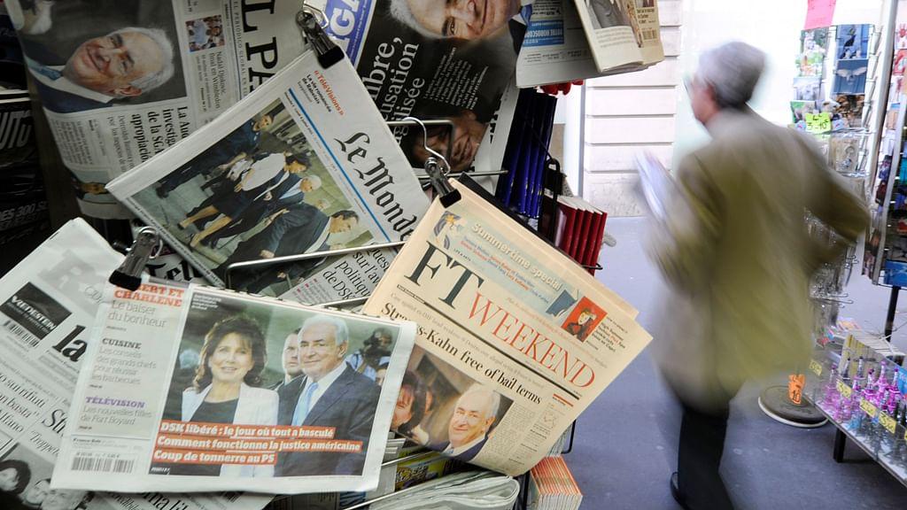Man walks past newspaper kiosk. (Photo: Reuters)