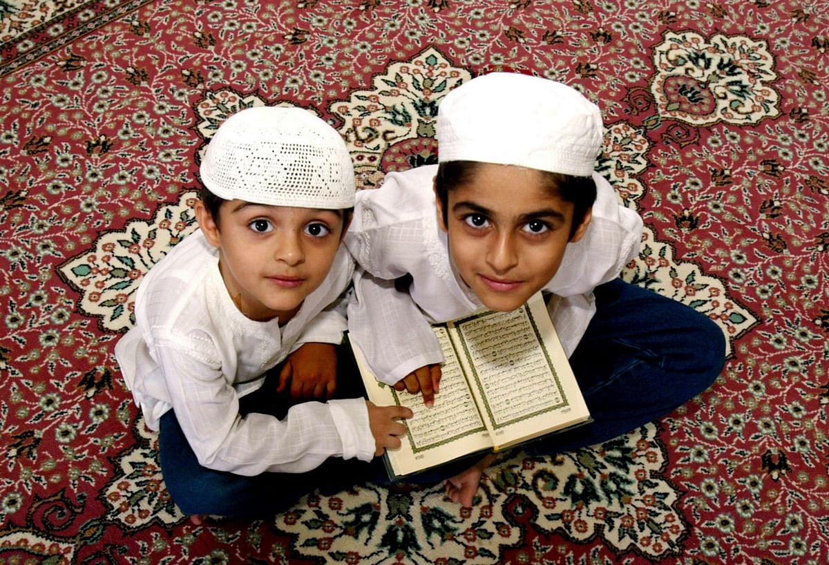 Muslim boys recite the holy Koran after a special prayer to mark the Eid-Milad festival in Dubai April 20, 2005. Muslims around the world today celebrate Eid-Milad, the anniversary of the birth of Prophet Mohammed, by offering special prayer. (Photo: Reuters)