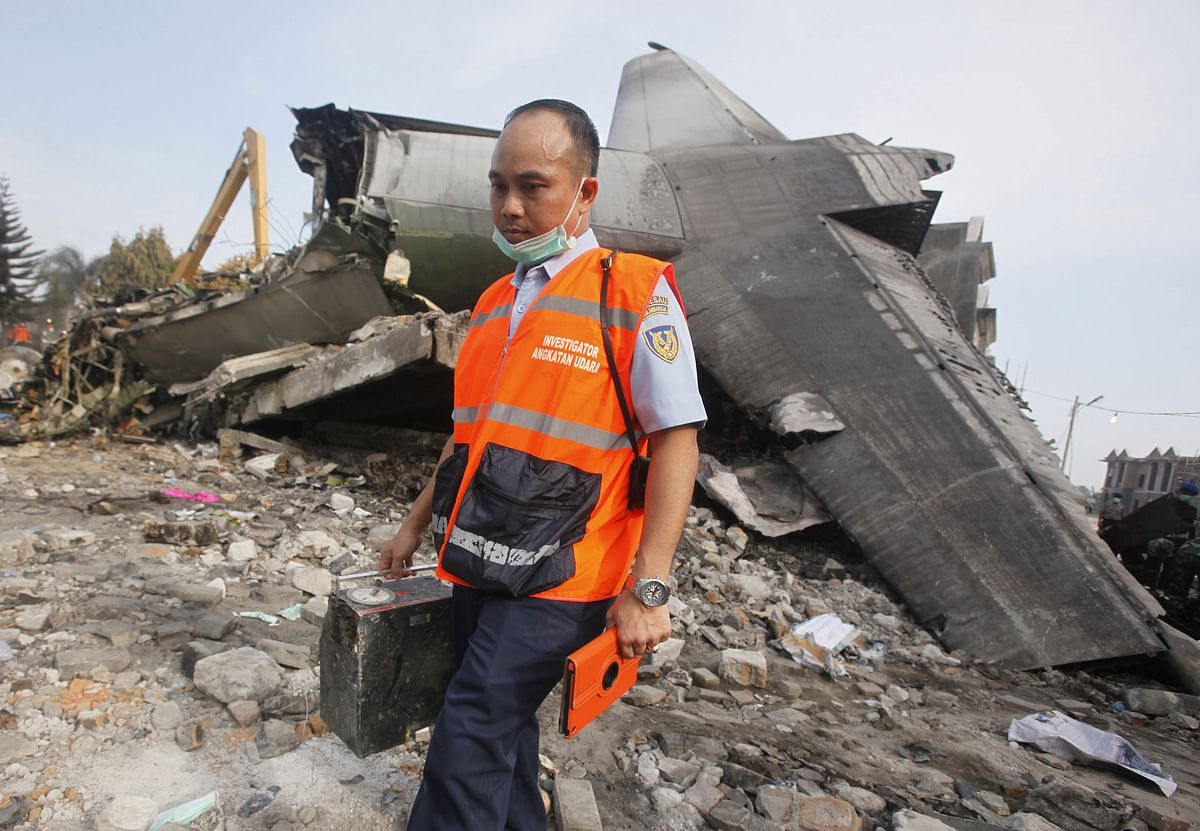 An investigator walks past the wreckage of the crashed air force transport plane in Medan inIndonesia. (Photo: AP)