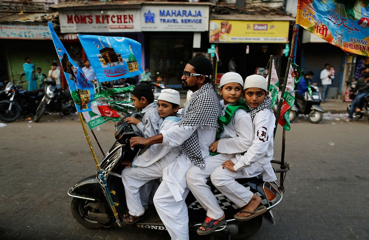 Muslims ride on a scooter on their way to participate in a procession to mark Eid-e-Milad-ul-Nabi, or birthday celebrations of Prophet Mohammad in Mumbai January 14, 2014. (Photo: Reuters)