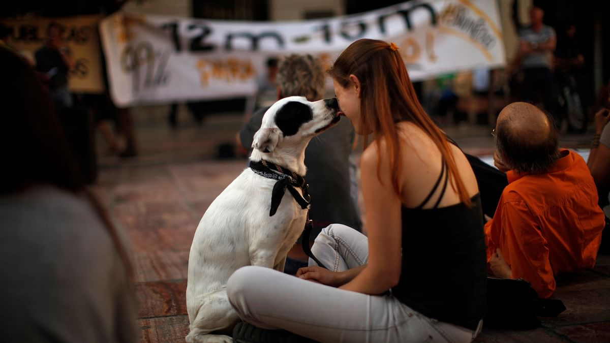 A woman getting licked by her pet dog in Spain. (Photo: Reuters)