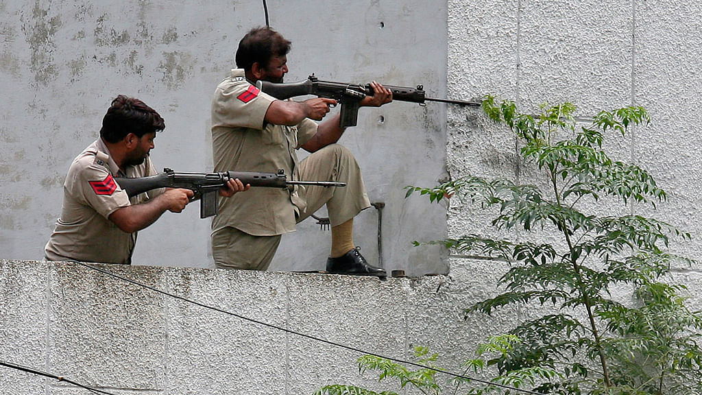 Policemen take their positions next to a police station during a gunfight at Dinanagar town in theGurdaspur district of Punjab. (Photo: Reuters)