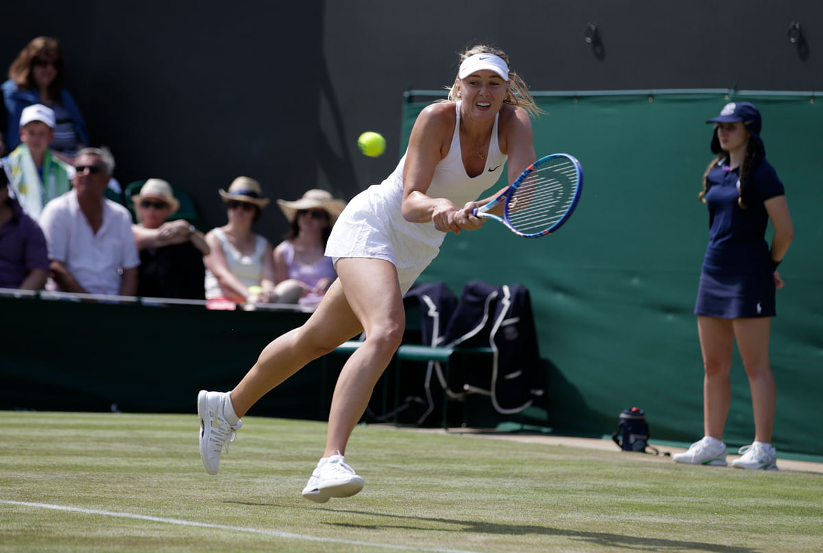 Maria Sharapova of Russia returns a shot to Richel Hogenkamp of the Netherlands, during their singles match at the All England Lawn Tennis Championships in Wimbledon. (Photo: AP)