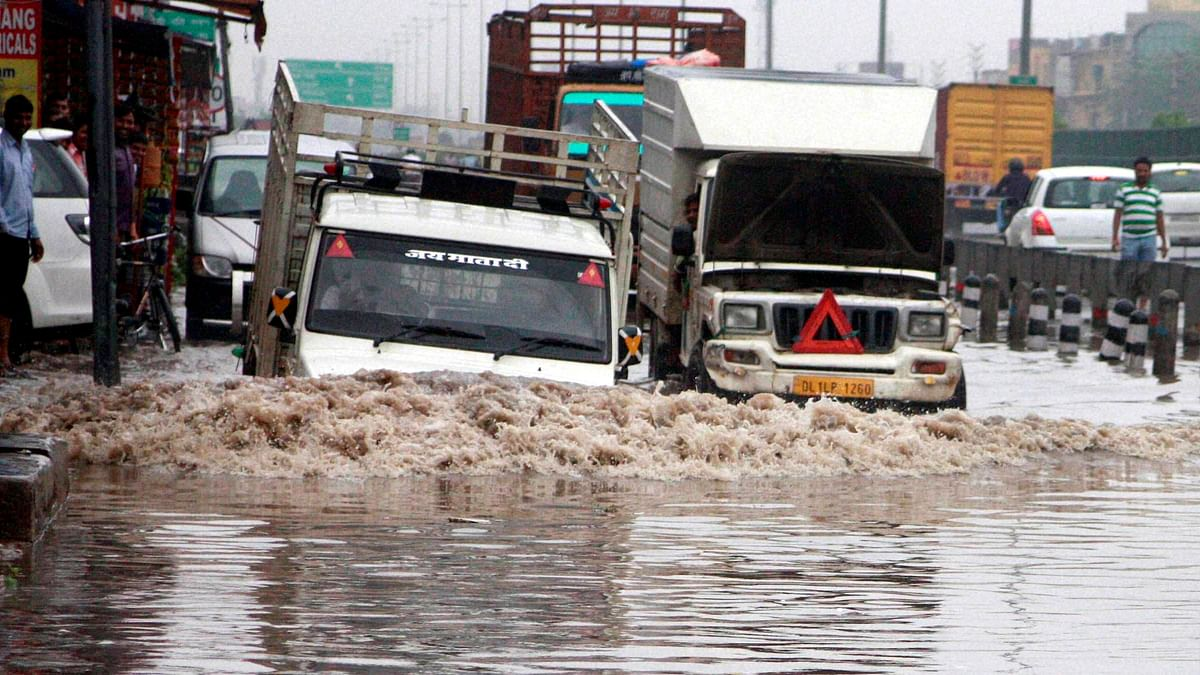 Vehicle moves through a water logged road after heavy rains in NCR region on Saturday. (Photo: PTI)