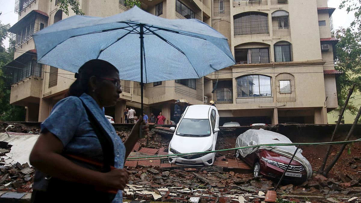 A woman walks past the remains of a wall that collapsed  due to heavy rains in Mumbai on July 21, 2015. (Photo: Reuters)