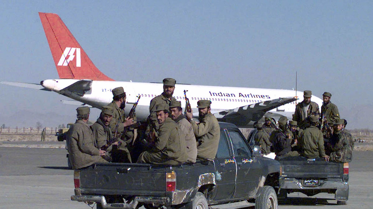Armed soldiers from the Taliban Islamic militia race towards the hijacked Indian Airlines plane at Kandahar airport.