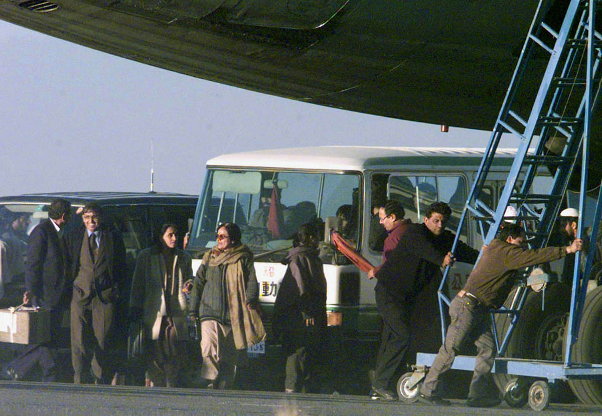 Freed passengers of the hijacked Indian Airlines plane prepare to board a minibus as workers push a staircase away from the plane at Kandahar airport