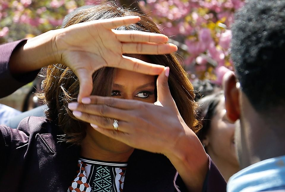 US first lady Michelle Obama obliges cheering students by showing off the hand signal the students in the quadrangle dormitory use to identify themselves