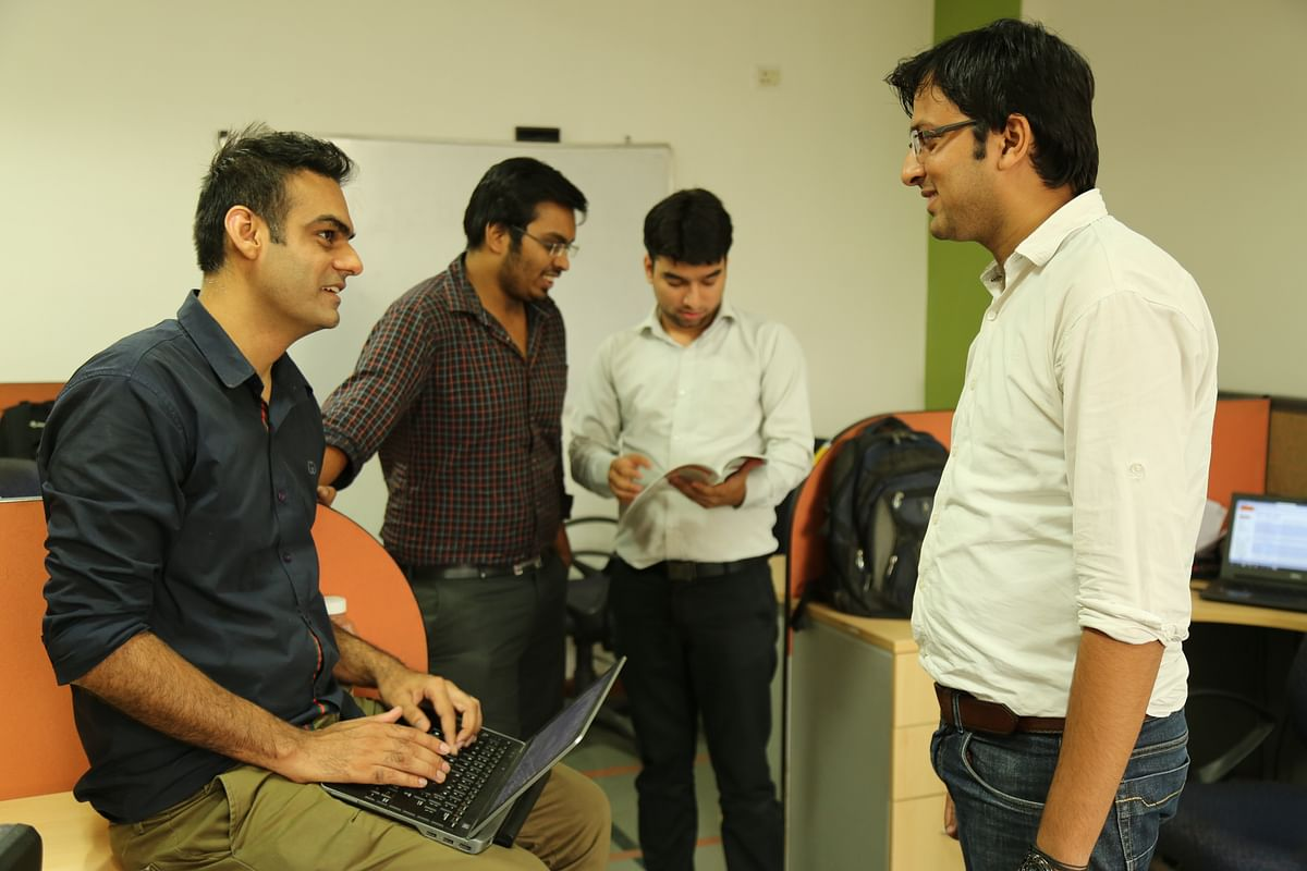 The team at QuickCompany talking a few minutes down time. (Photo: TheQuint)