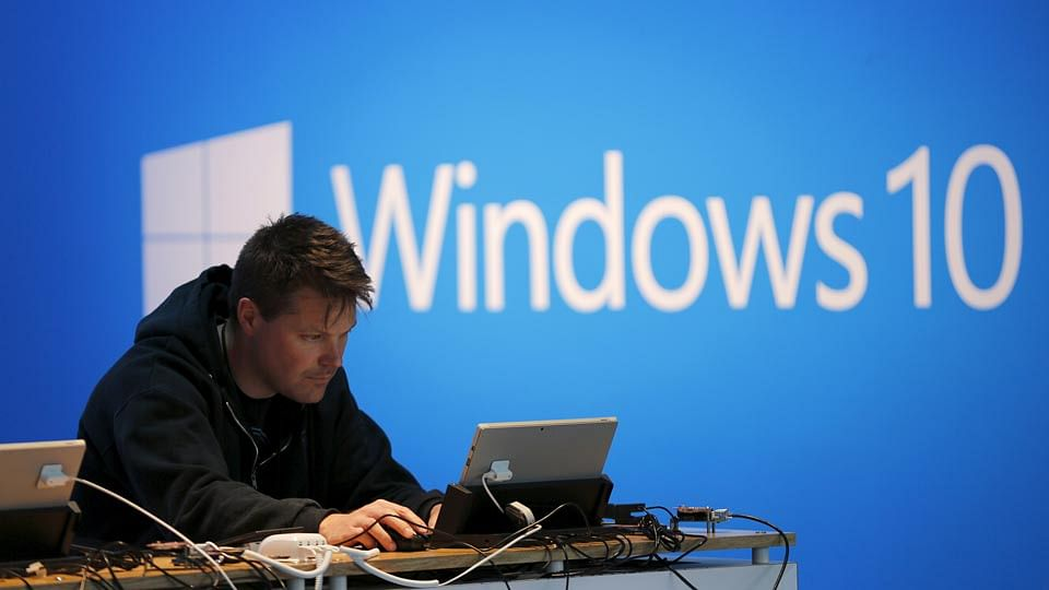 A man works on a laptop computer near a Windows 10 display at Microsoft Build in San Francisco.