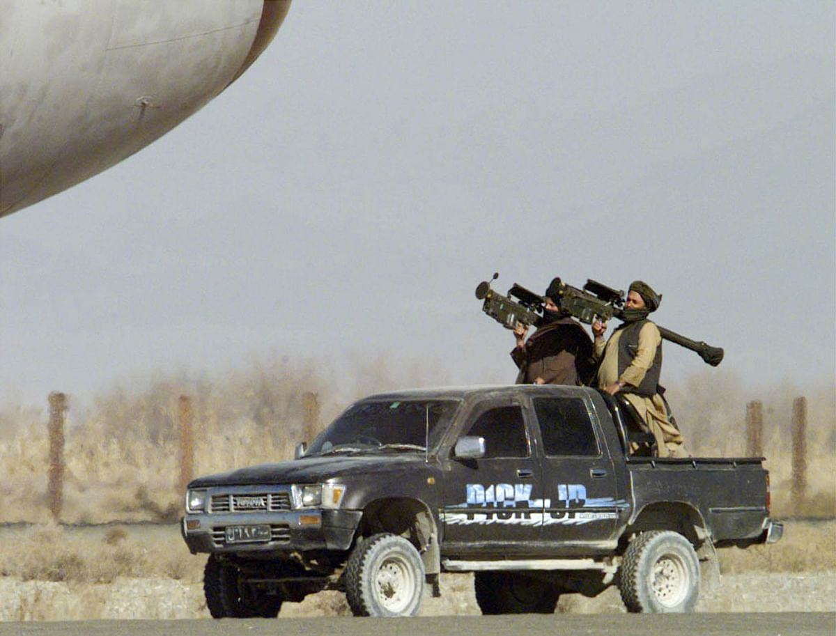 Two Taliban militiamen, with U.S.-made Stinger surface-to-air missiles upon their shoulders standby close to the hijacked Indian airliner at Kandahar airport