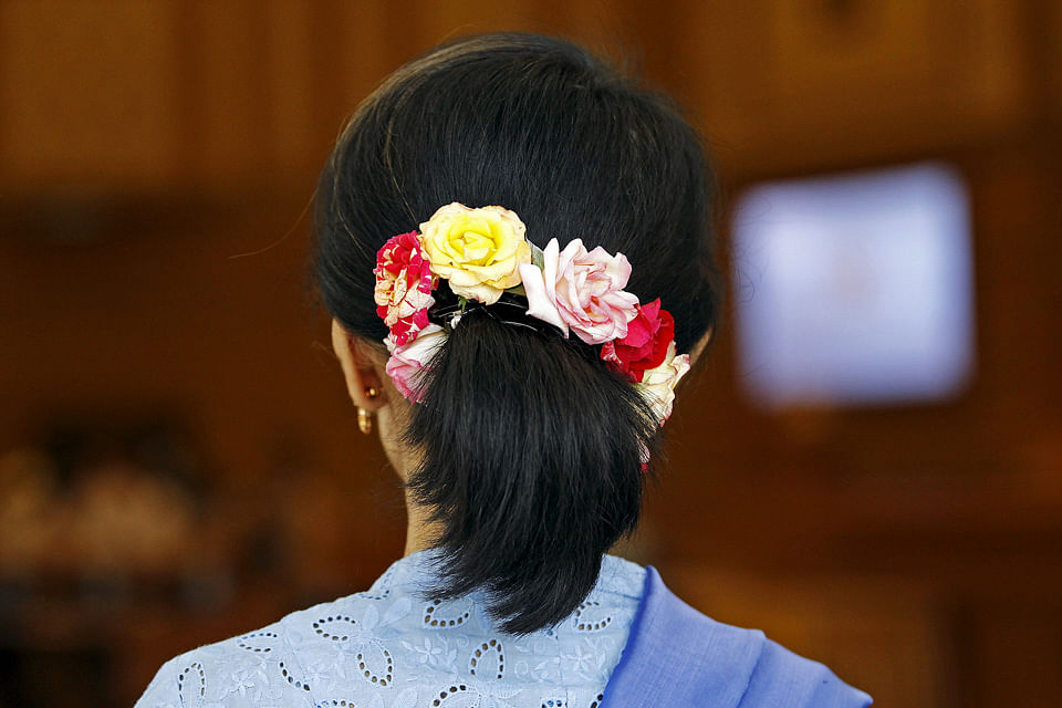 Myanmar's pro-democracy leader Aung San Suu Kyi, wearing her trademark flowers in her hair, arrives for a session of parliament in Naypyidaw. (Photo: Reuters)