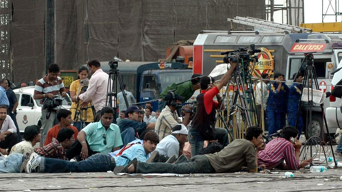 Journalists take cover during a gunfight between terrorists and NSG commandos outside Taj Hotel on November 28, 2008. (Photo: Reuters)