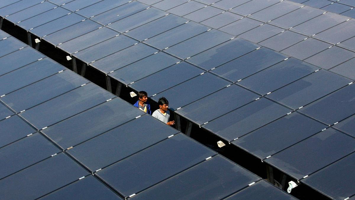 Workers walk between rows of solar photovoltaics, inside a solar power plant at Raisan village near Gandhinagar. (Photo: Reuters)