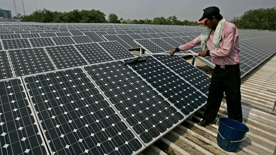 A solar panel is cleaned using a wet sponge. (Photo: iStock)