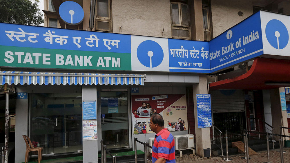 A man walks past a State Bank of India ATM in Mumbai.