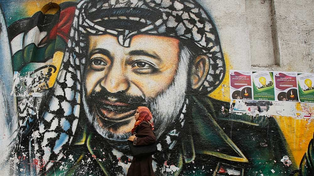 A Palestinian student walks past a mural depicting late Palestinian leader Yasser Arafat in Gaza City (Photo : Reuters)