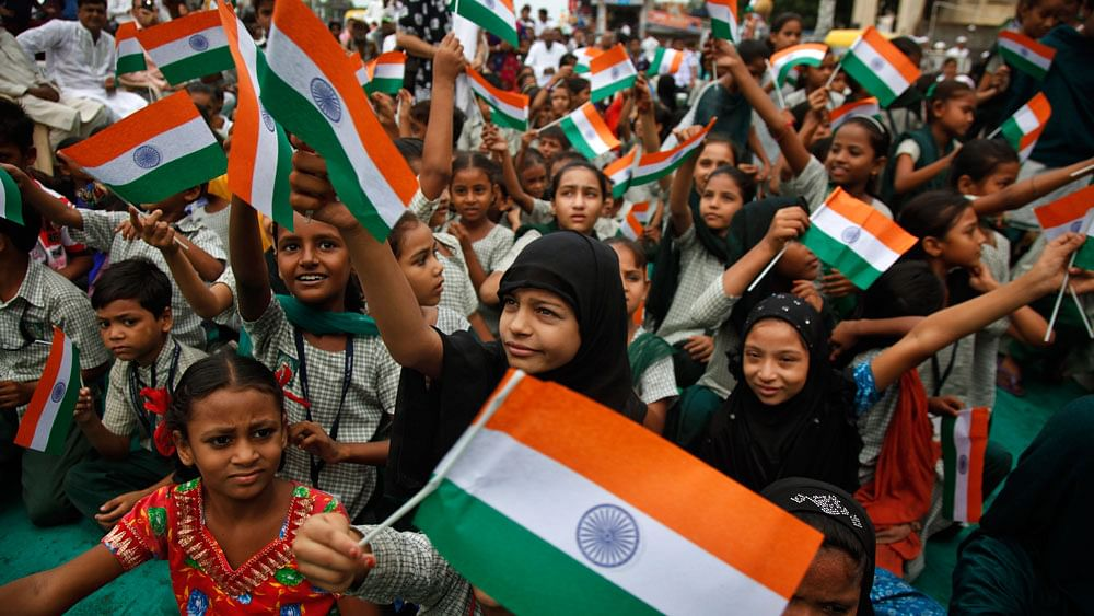 """<div class=""""paragraphs""""><p>People wave flags to mark Independence Day. </p></div>"""