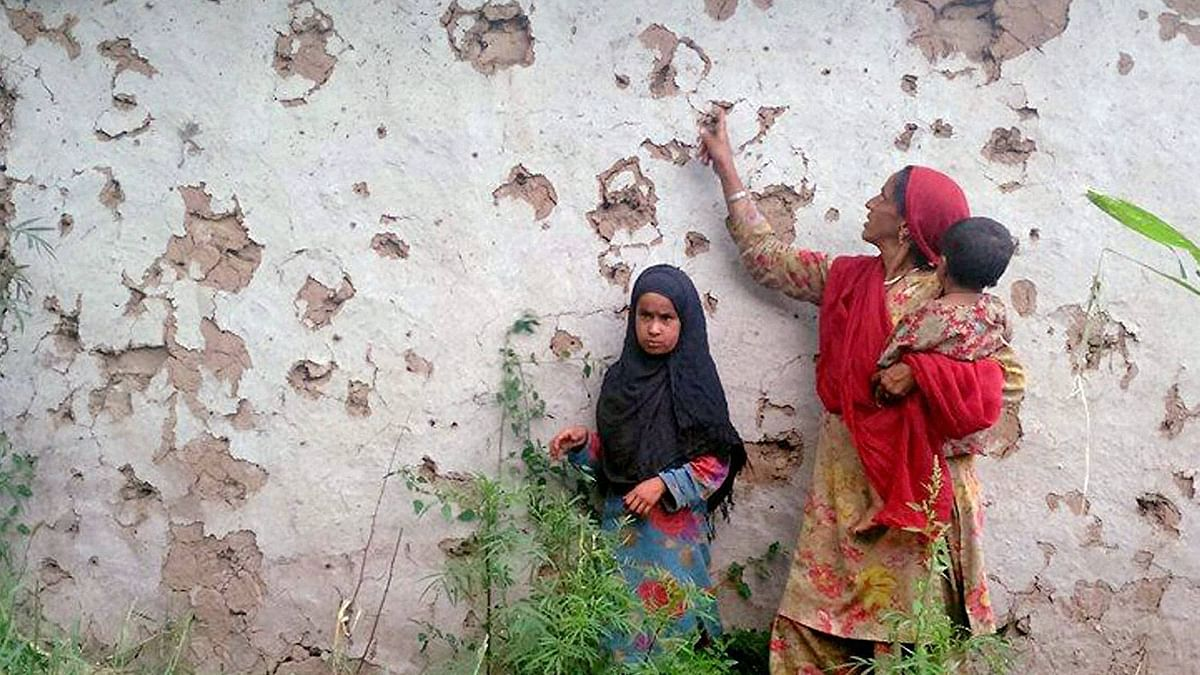 Villagers look at splinter marks on a house after a ceasefire violation by Pakistan in the Shahpur sector near the Line of Control in Jammu and Kashmir's Poonch district. (Photo: PTI)