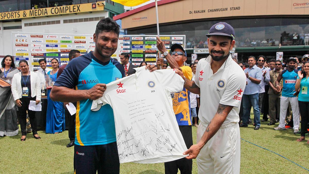 Virat Kohli, right, presents a souvenir to Sri Lankan cricketer Kumar Sangakkara at the end of his farewell test. (Photo: AP)